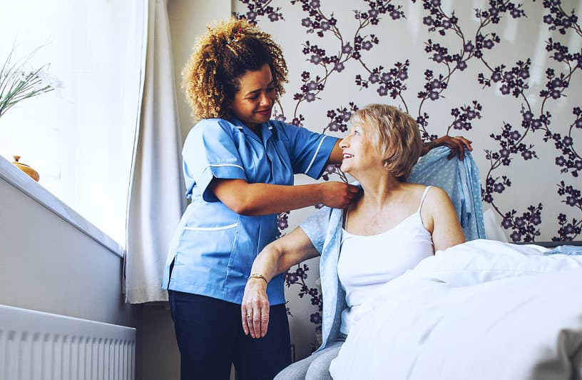 caregiver helping senior woman to wear a clothes
