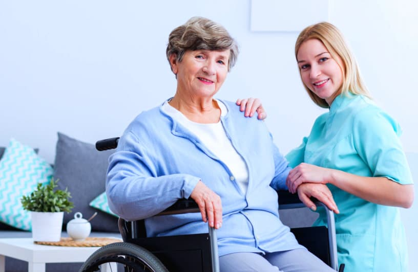 caregiver and senior woman with wheelchair are smiling